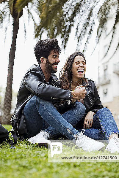 Spain  Barcelona  laughing young couple sitting on meadow