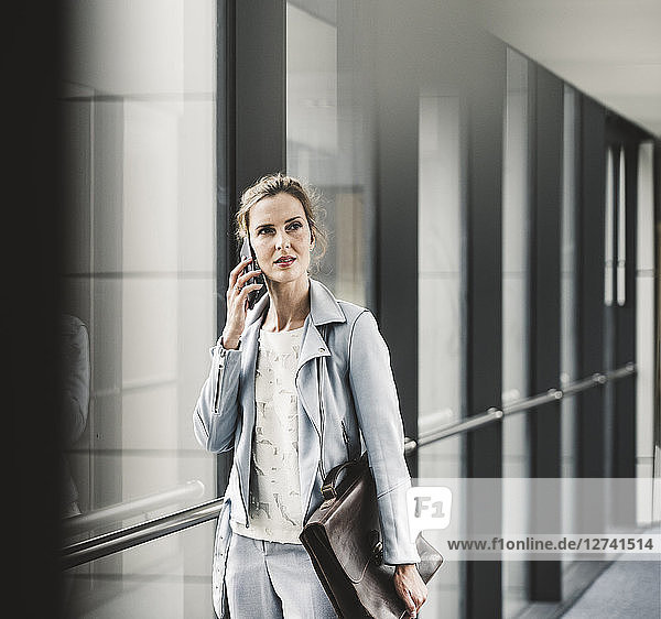 Businesswoman on cell phone at the window in office passageway