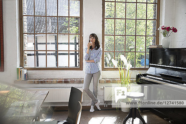 Woman standing at window of her loft apartment  drinking coffee