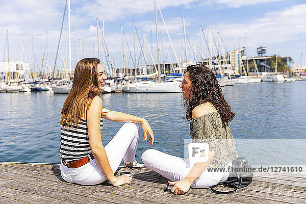 Two happy female friends talking at a marina