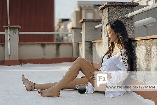 Young woman relaxing on roof terrace at sunset