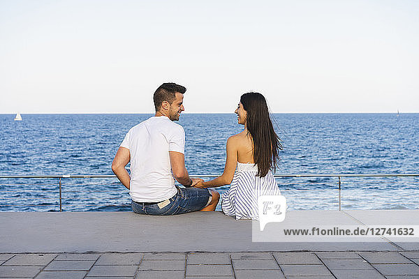 Happy young couple standing by the sea