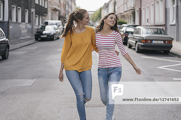 Two girlfriends having fun in the city  walking arm in arm