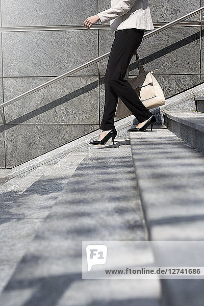 Businesswoman walking downstairs  partial view