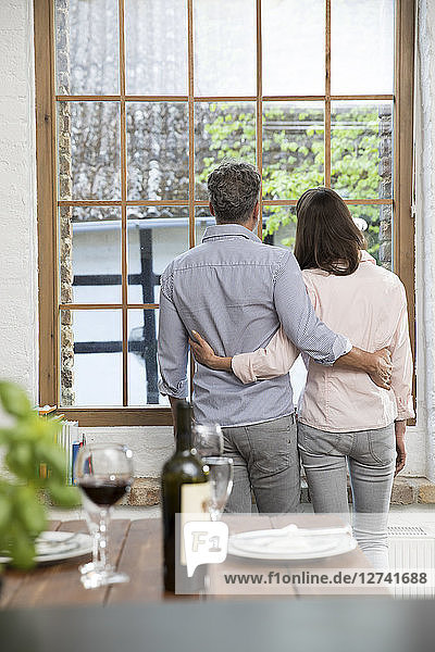 Mature couple standing in their comfortable loft  looking out of window  rear view