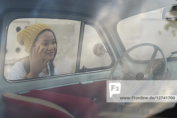 Young woman looking into small vintage car