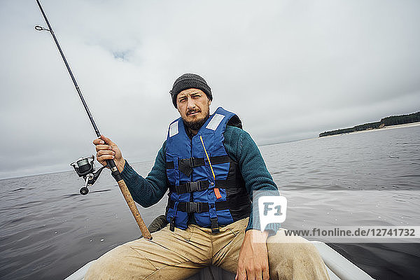 Man sitting on boat fishing with fishing rod