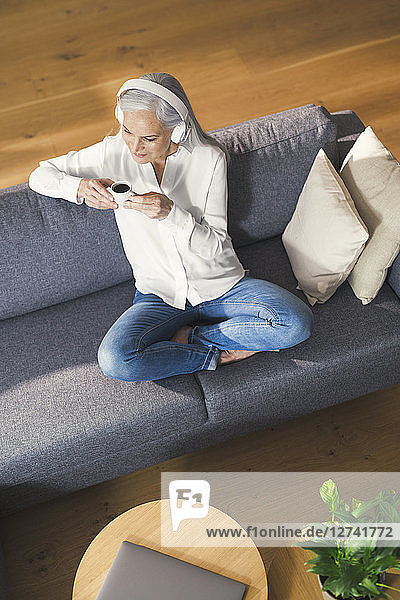 Senior woman sitting on couch  listen ning music an drinking coffee