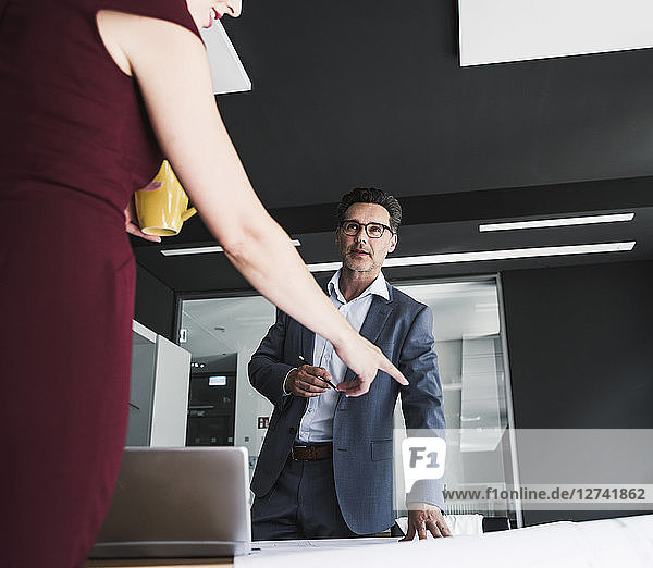 Businesswoman and businessman in office discussing with laptop and plan on desk