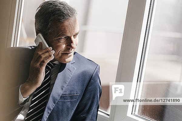 Smiling mature businessman on cell phone looking out of window