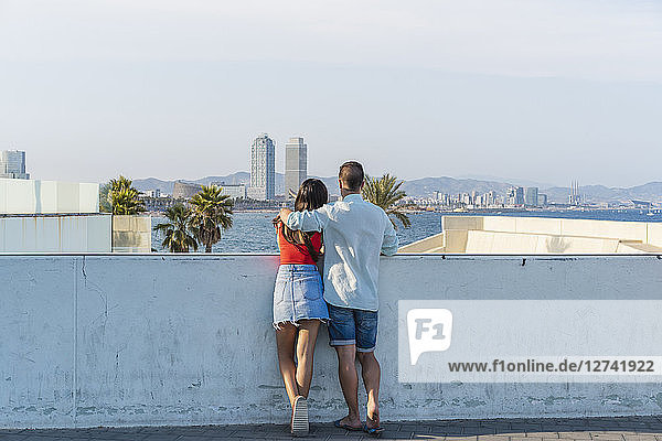 Young couple standing at wall  looking at view