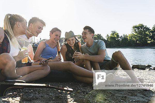 Group of happy friends sitting at the riverside with drinks and cell phone