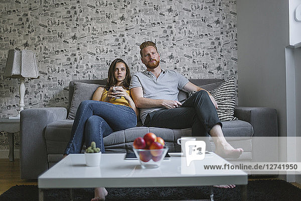 Young couple sitting on couch watching TV
