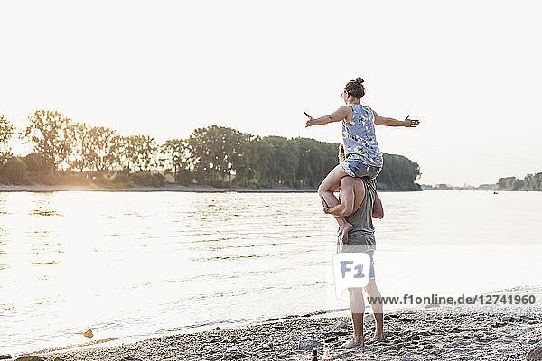 Young man carrying girlfriend on shoulders at the riverbank