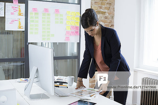 Businesswoman at desk in office looking at printouts