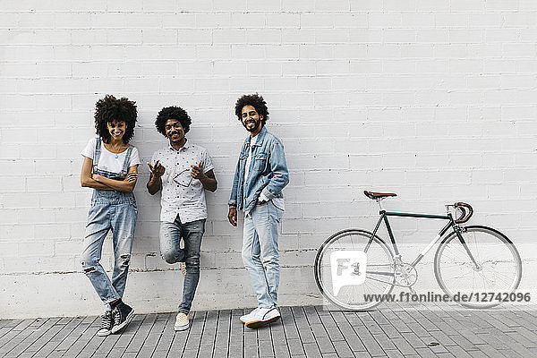 Group of three friends with racing cycle leaning against wall