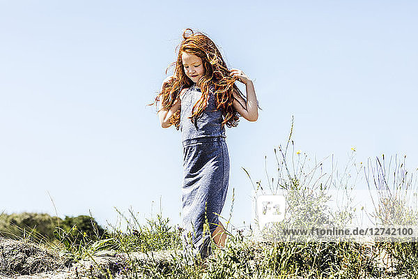 Netherlands  Zandvoort  redheaded girl walking in dunes