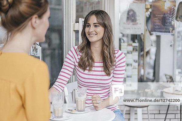 Two girlfriends meeting in a coffee shop  talking
