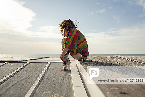 Woman with tattoo crouching on plank  looking at the sea