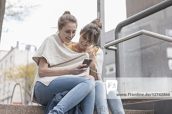 Friends sitting on stairs in the city  using smartphone
