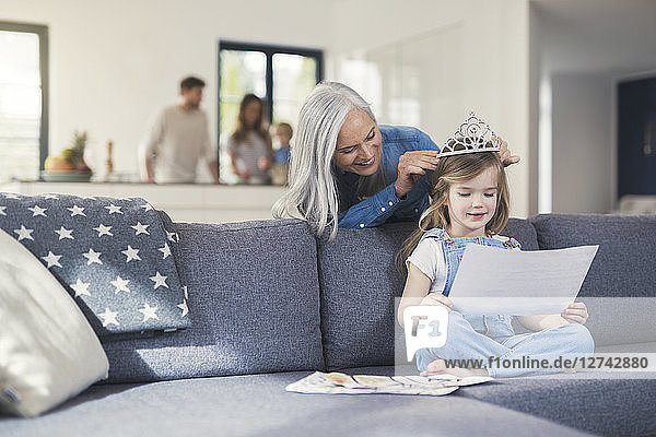 Grandmother playing with granddaughter  puuting crown on her head