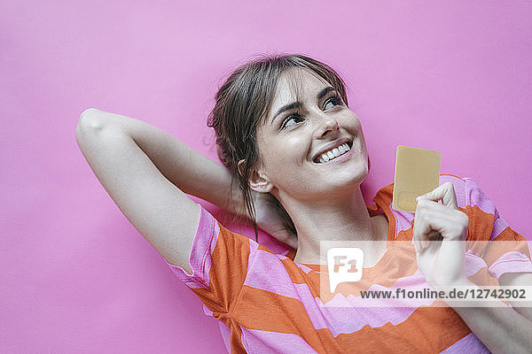 Woman lying on pink background with hands behind head  holding credit card