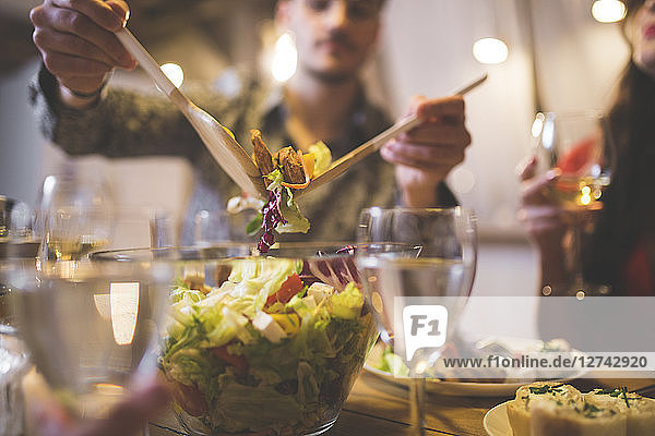Man serving salad at dinner with family and friends