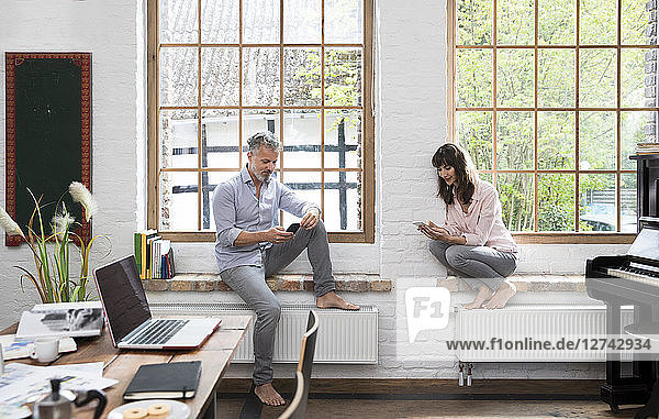 Mature couple working barefoot on window sill of home office  using smartphones