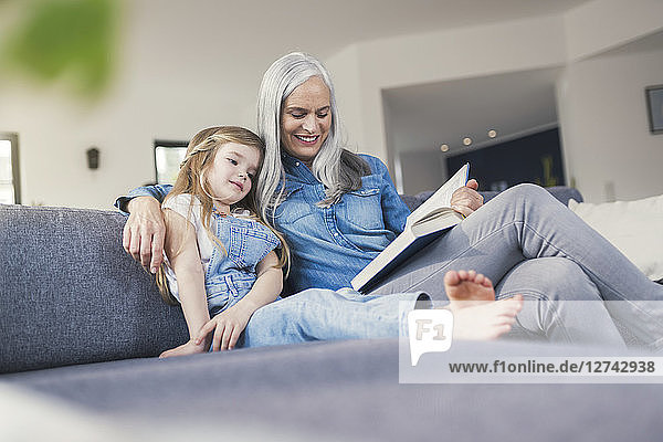 Grandmother and granddaughter sitting on couch  reading together