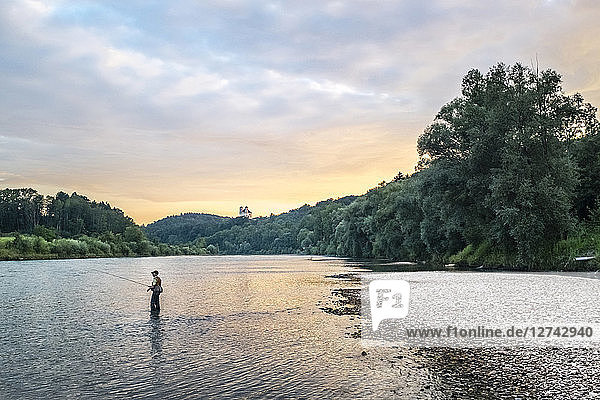 Germany  Upper Bavaria  Burghausen  Salzach valley  fly fisherman at sunset