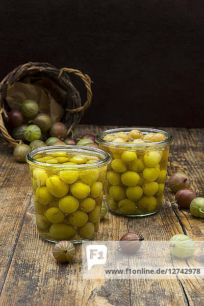 Two jars of preserved gooseberries and gooseberries on wood