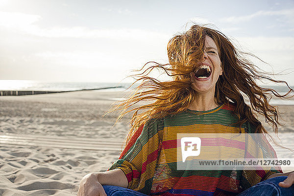 Woman sitting on the beach  screaming for joy