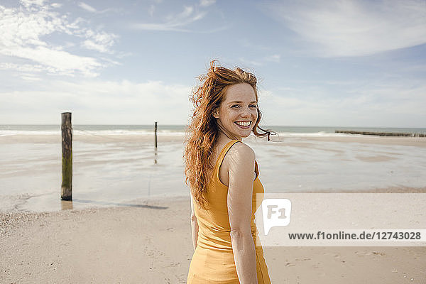 Portrait of a redheaded woman  laughing happily on the beach
