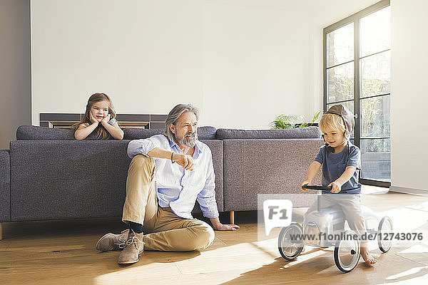 Grandfather playing with grandchildren  sitting on toy car