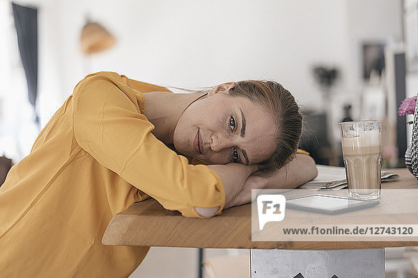 Young woman with digital tablet resting on table in a coffee shop