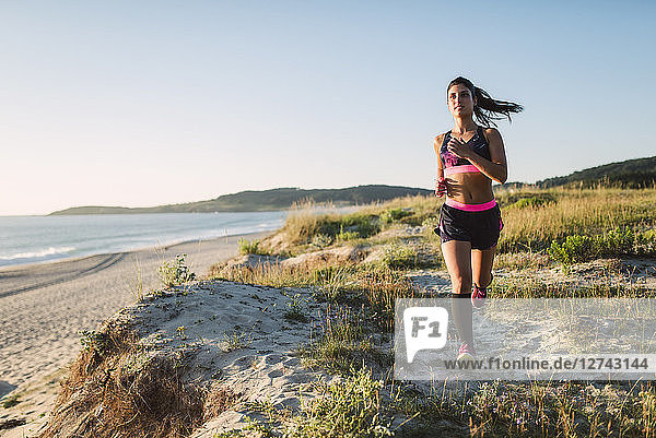 Young sportswoman training on the coast  jogging