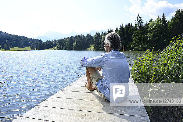 Germany  Mittenwald  mature man relaxing on jetty at lake