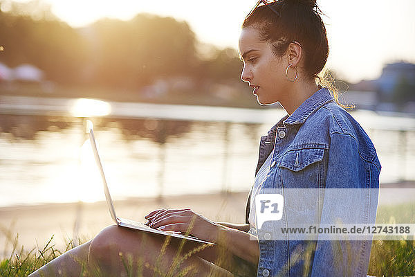 Young woman sitting on a meadow at evening twilight using laptop