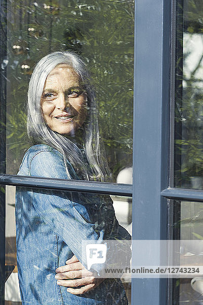 Senior woman looking out of window  smiling