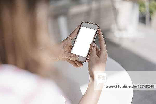 Young woman sitting in coffee shop  using smartphone