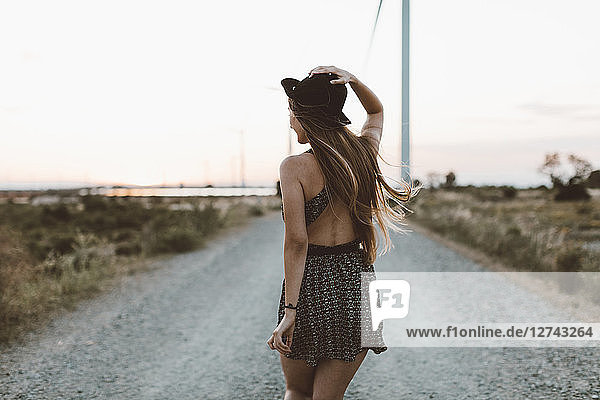 Back view of young woman walking on rural road in the evening