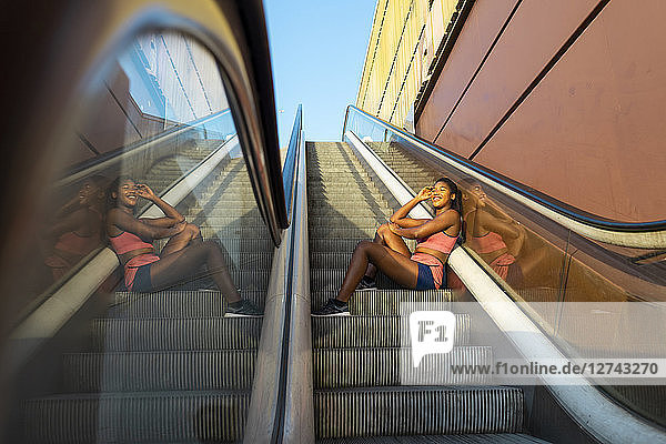 Young sportive woman sitting on escalator