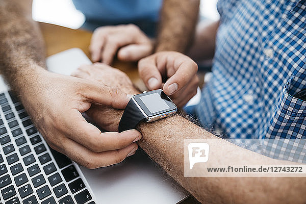 Adult grandson teaching his grandfather to use smartwatch  close-up