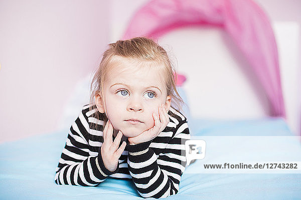 Portrait of daydreaming little girl lying on bed at home