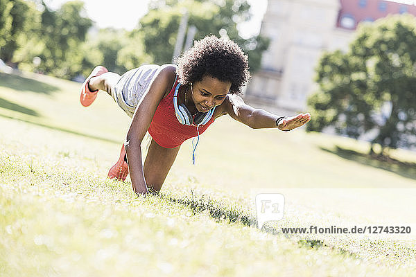 Young woman exercising on meadow in park