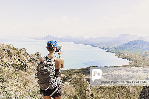 Mauritius  Riviere Noire District  Woman photographing with smartphone the coast  view from Mount Le Morne Brabant