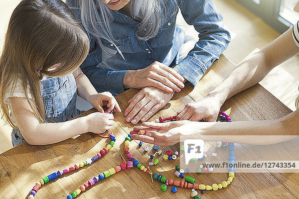 Grandmother and granddaughter and mother threading beads