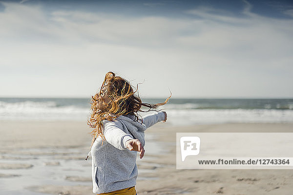 Redheaded woman relaxing on the beach  with arms outstretched