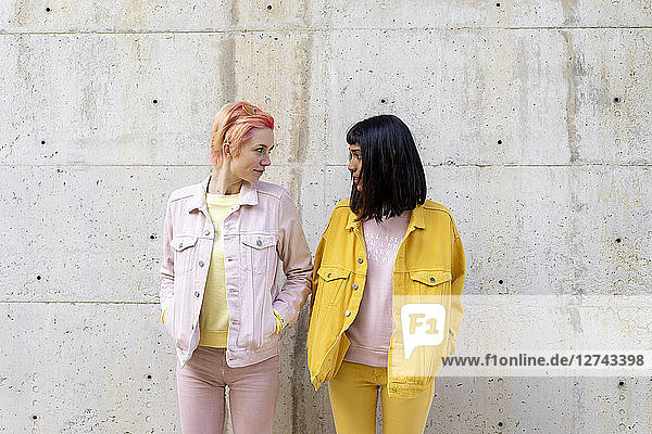 Two alternative friends having fun  wearing yellow and pink jeans clothes  face to face