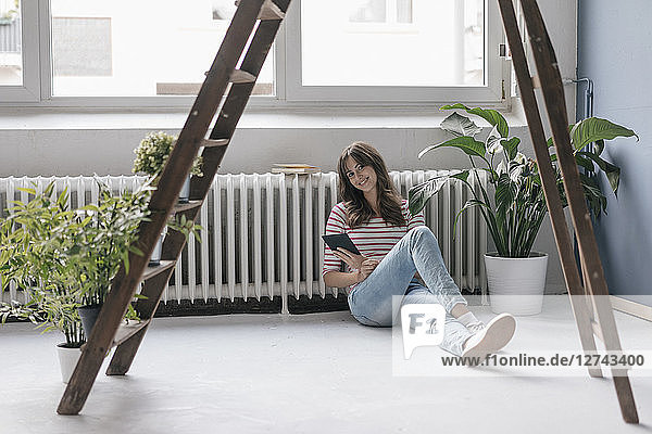 Woman sitting on ground in her new home  reading e-book  surrounded by plants